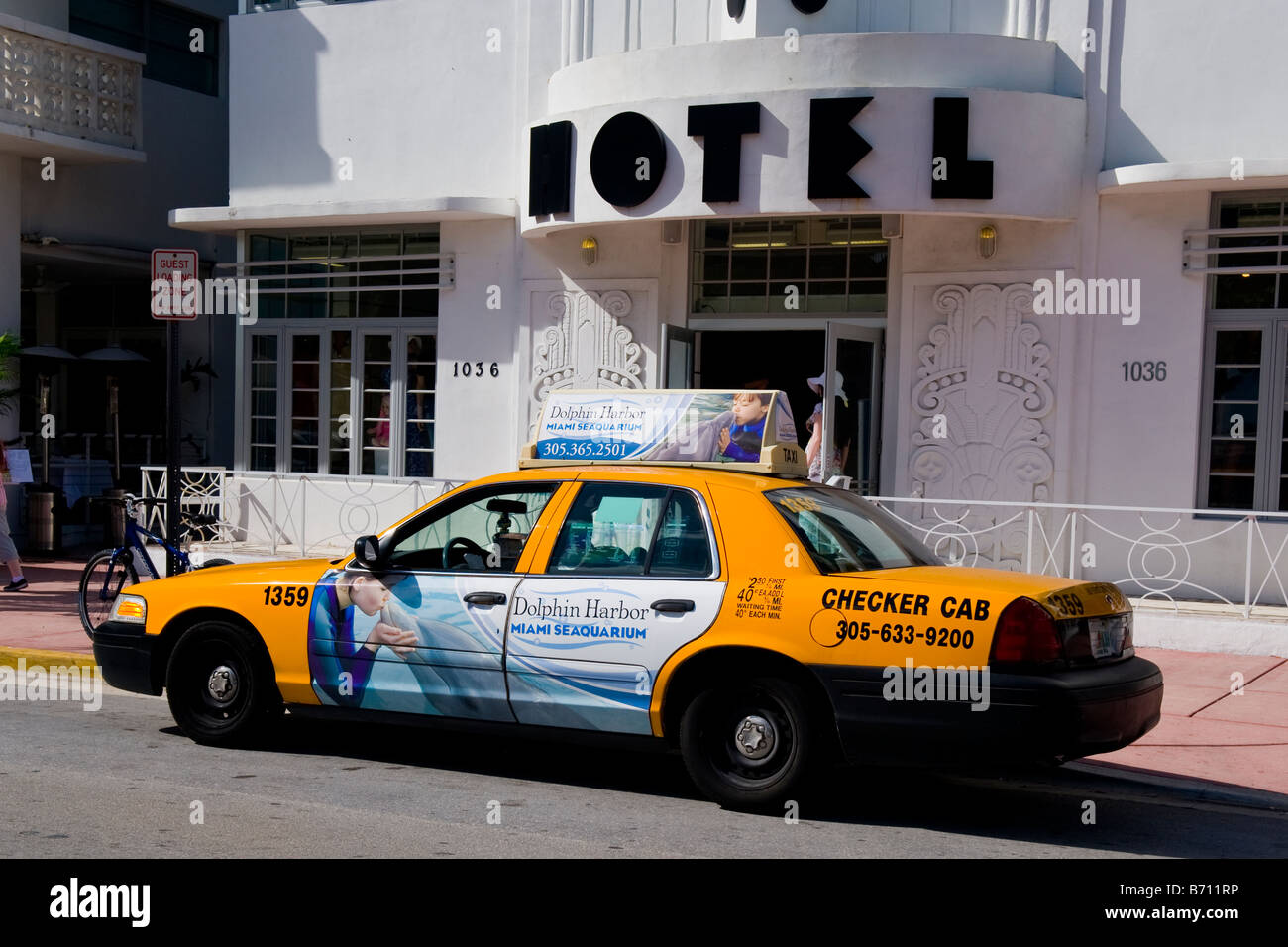 Miami South Beach Ocean Drive Checker Yellow Taxi Cab Car With Adverts Awaits Fare Outside Art Deco Hotel Congress Entrance