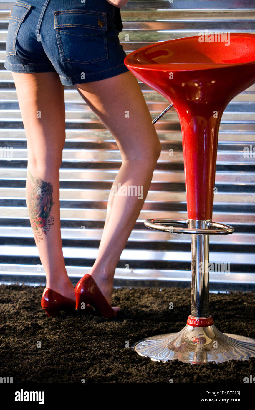 Rear View Of Tattooed Legs Of Woman Standing By Red Stools