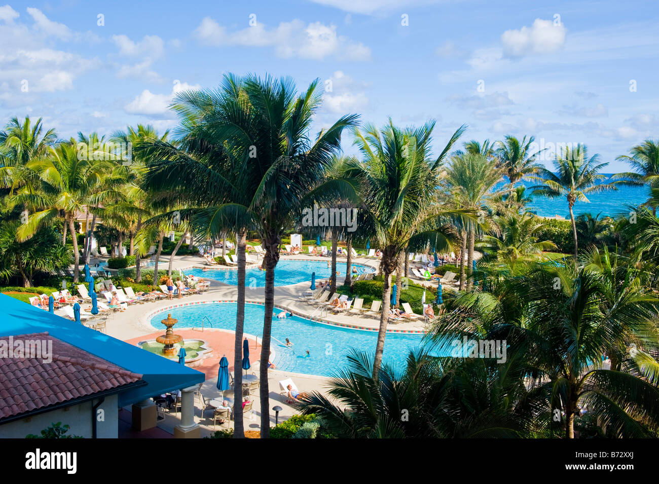 palm beach shores  marriott ocean pointe resort  scene of swimming poolwith palm trees  sea blue sky  clouds in background. palm beach shores  marriott ocean pointe resort  scene of