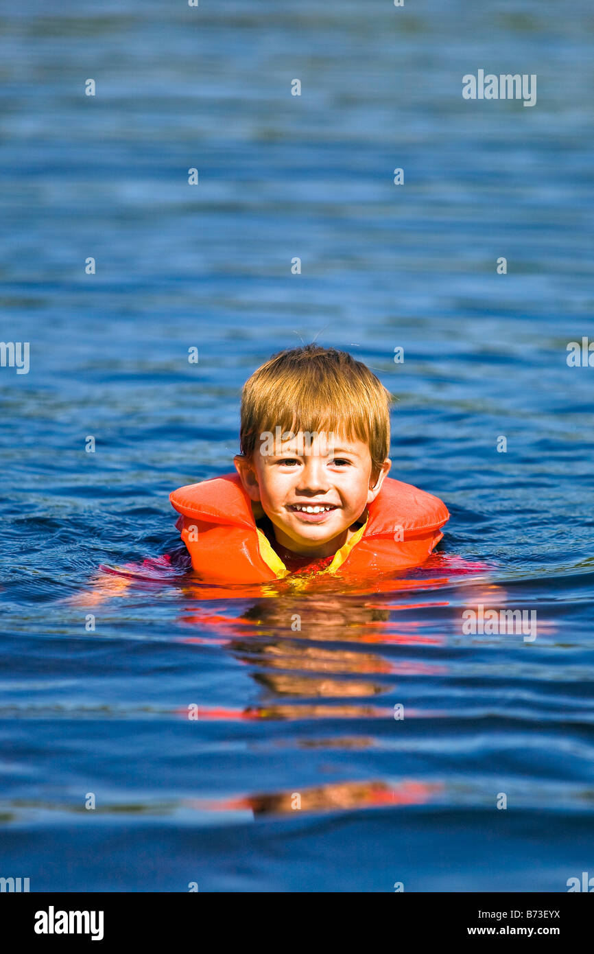 Two Year Old Boy Learning To Swim In Lake Wearing A Life Jacket Stock Photo Royalty Free Image