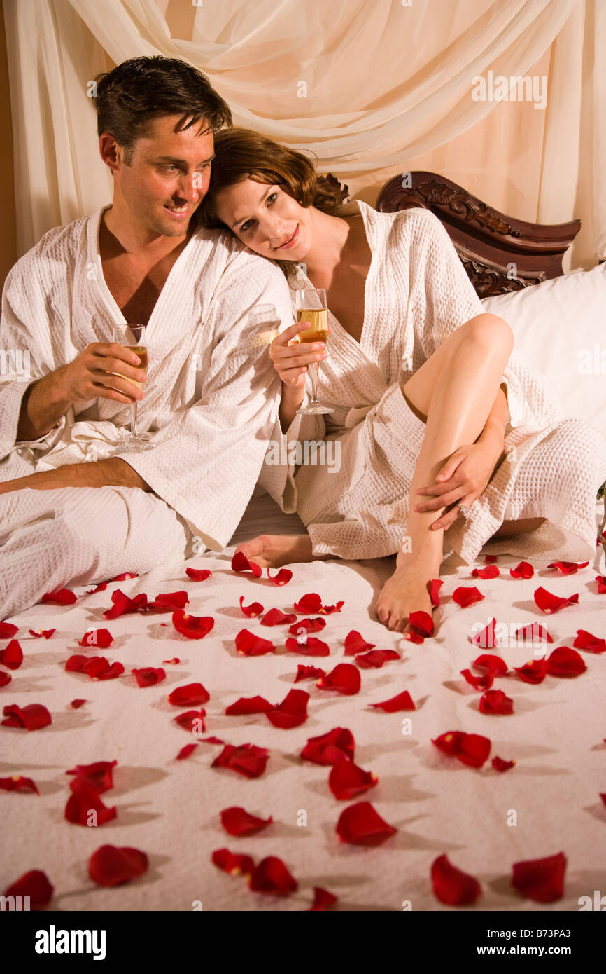 Romantic couple on bed sipping champagne surrounded by rose petals. Romantic couple on bed sipping champagne surrounded by rose petals