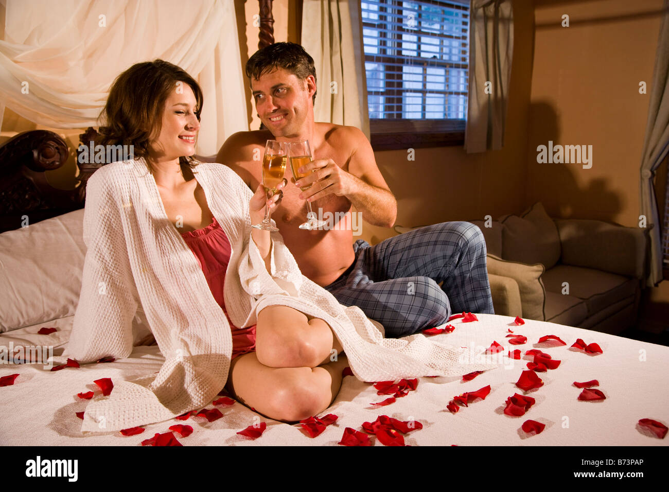 Romantic couple sitting on bed sipping champagne surrounded by rose petals. Romantic couple sitting on bed sipping champagne surrounded by
