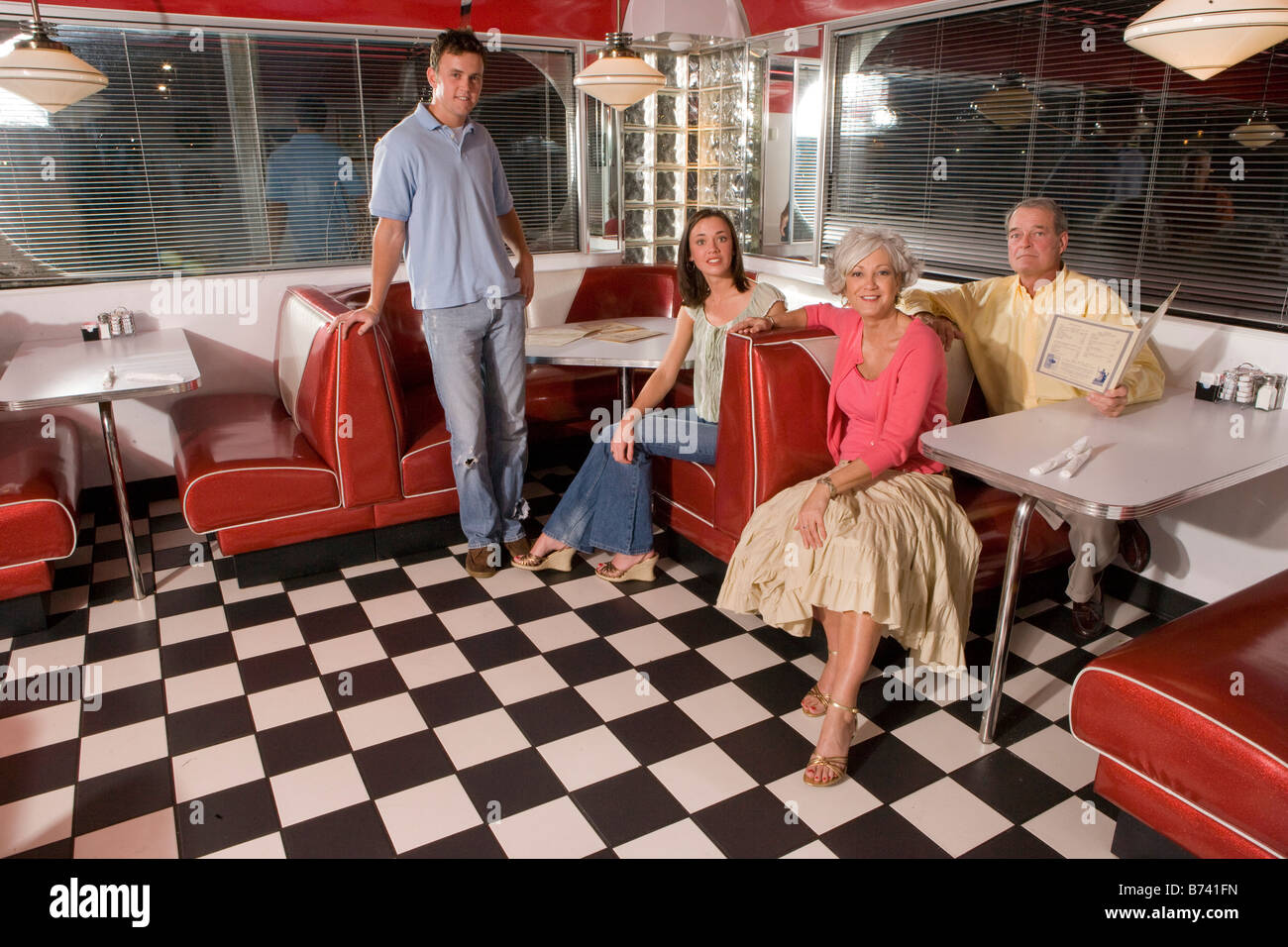 Young Couple With Parents Sitting In Booth Of Old