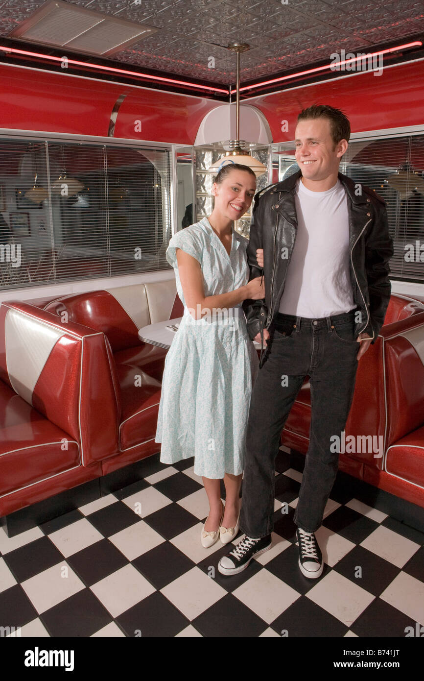 Portrait Of Young Couple Standing In Diner Wearing 1950s