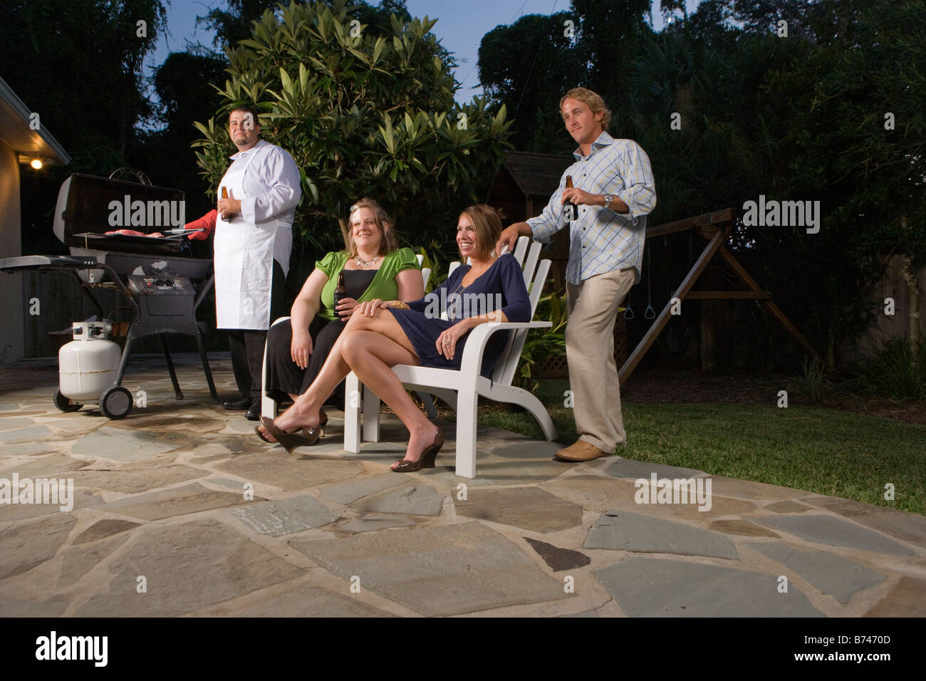 Four Friends Drinking Beer And Grilling On Backyard Patio