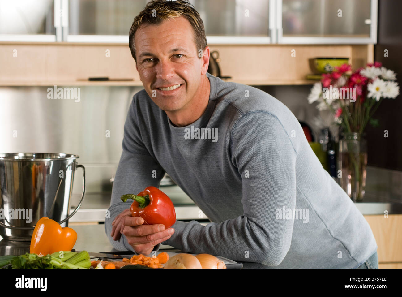 man with vegetables in kitchen with metal kitchen compost pail for collecting kitchen scraps winnipeg canada