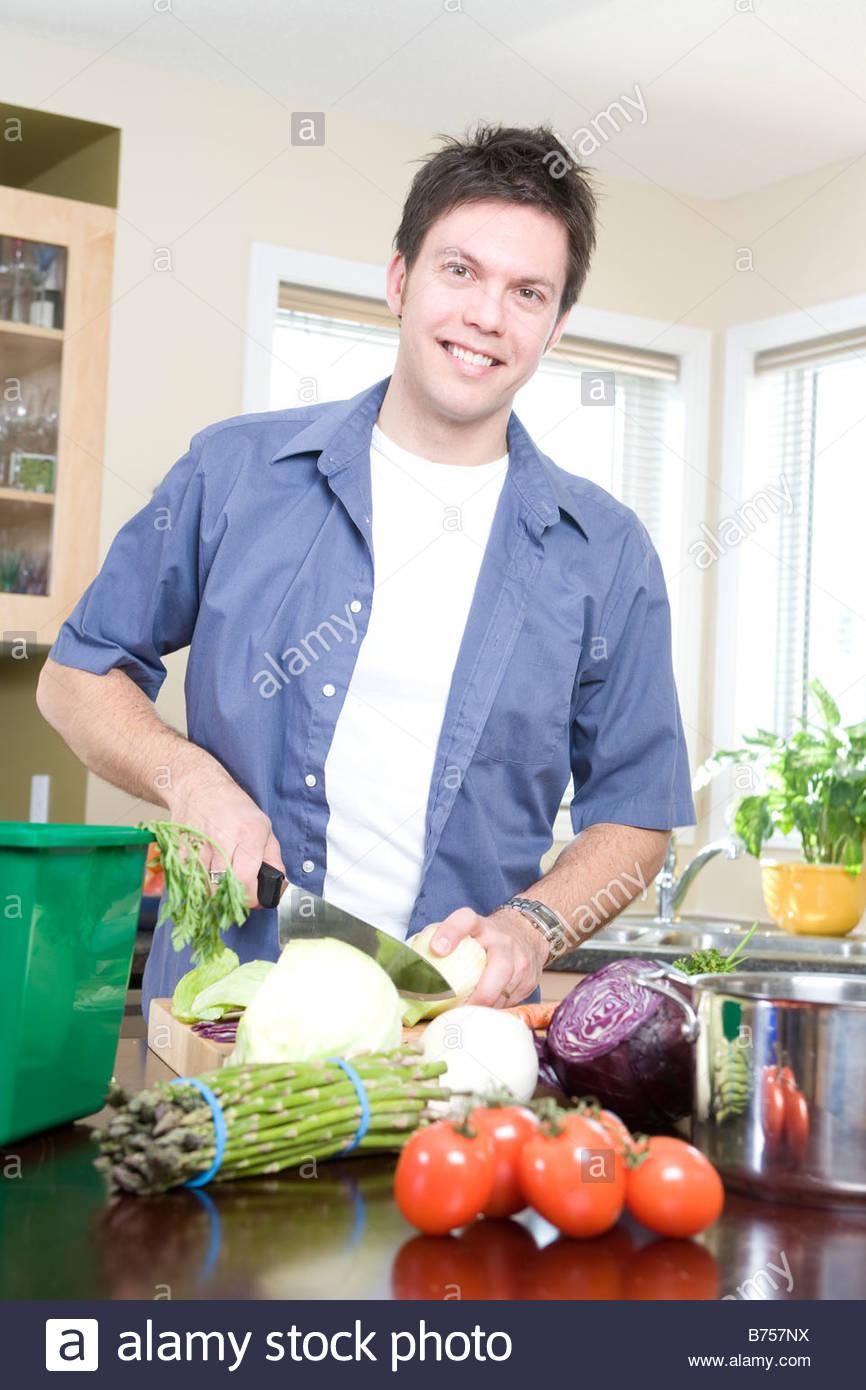 man in kitchen cutting vegetables beside kitchen compost bin winnipeg canada