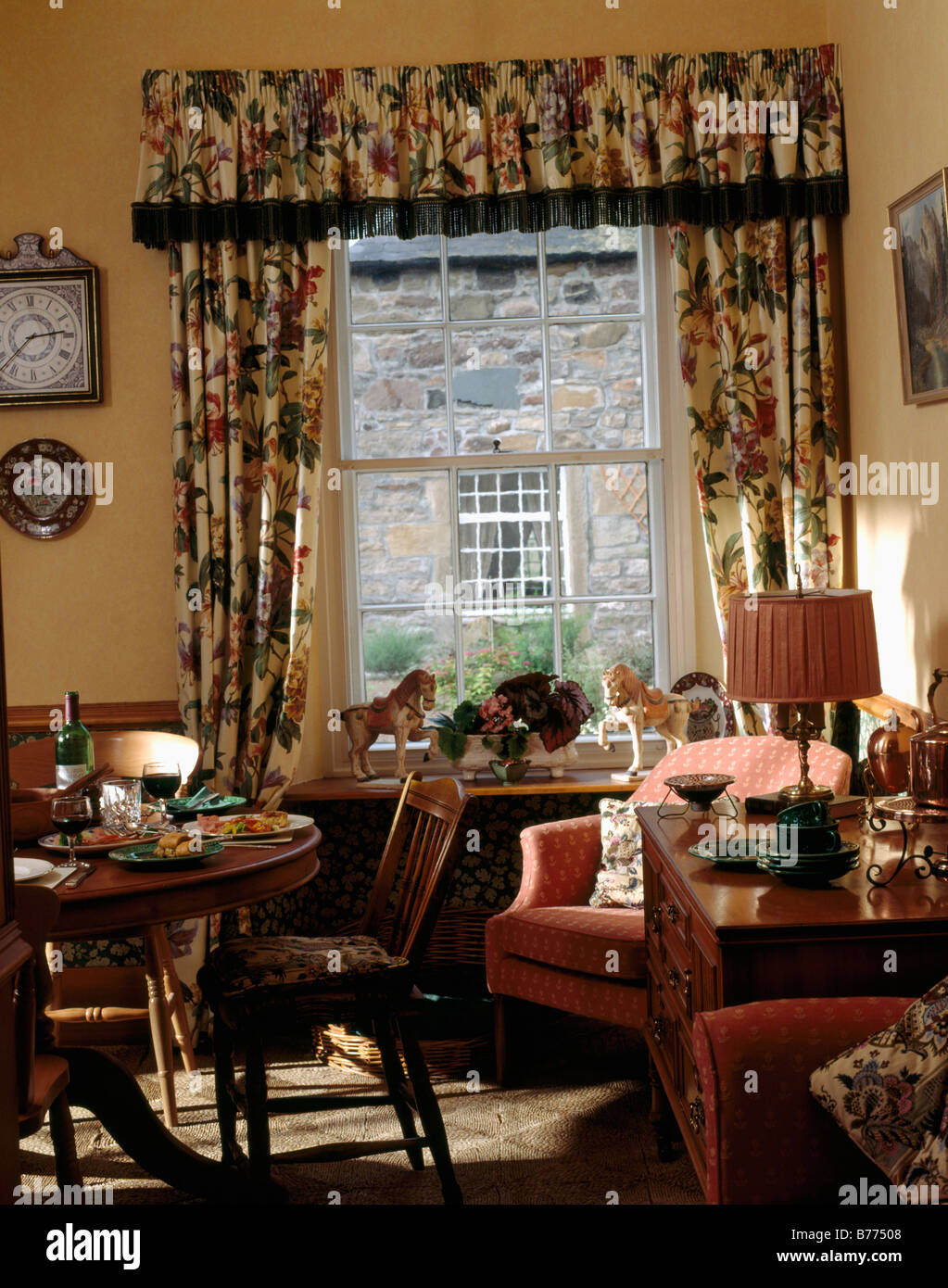 Floral Curtains And Pelmet At Window In Traditional Country Dining Room With Pink Armchair