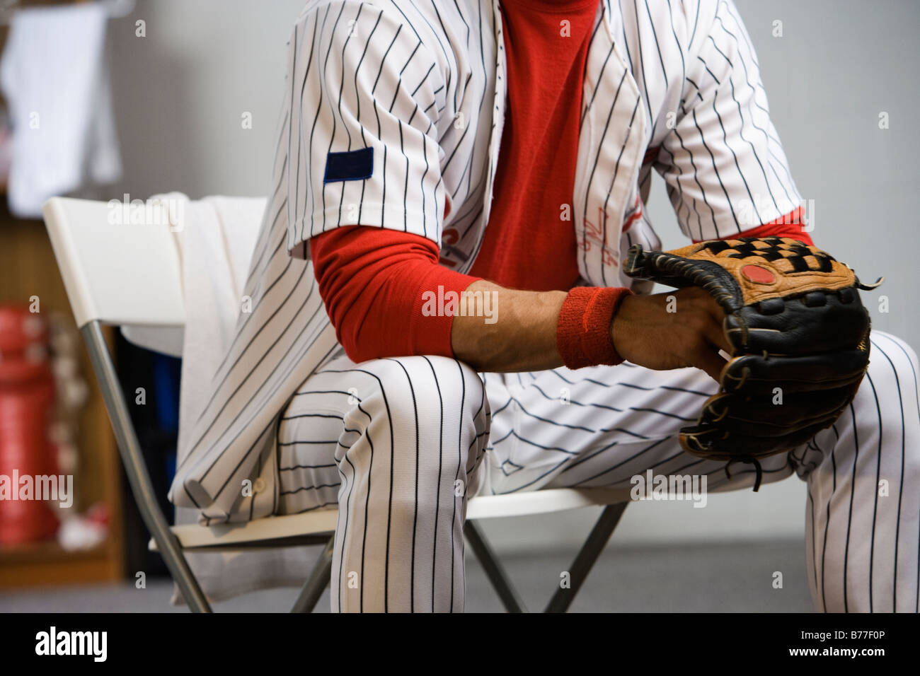 Baseball Player Holding Glove Locker Room