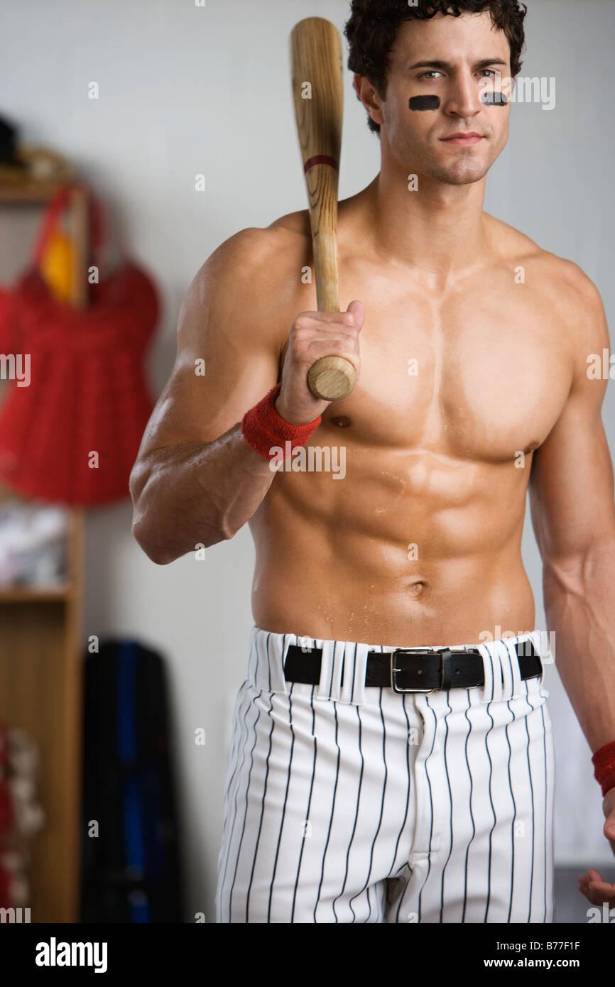 Portrait Of Baseball Player Bare Chest Holding Bat Locker Room