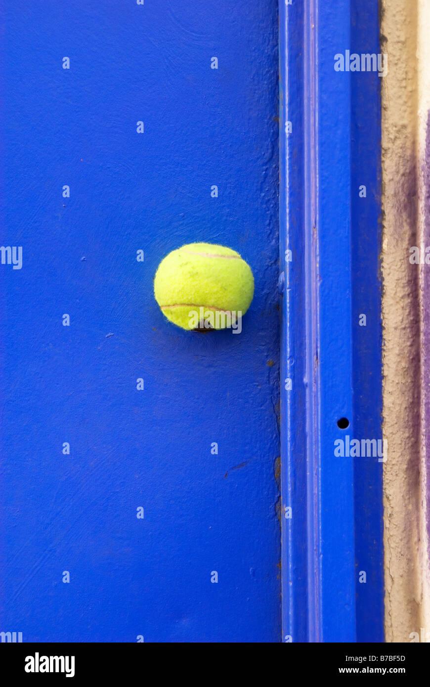 A tennis ball covers the door knob of a blue door Photo taken in ...