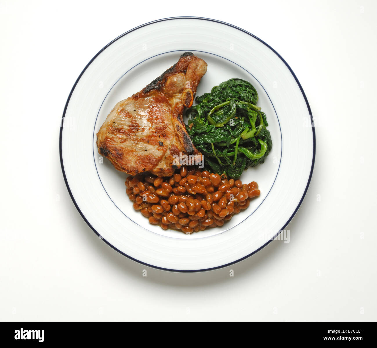 A cooked t-bone steak with baked beans and spinach on a ...