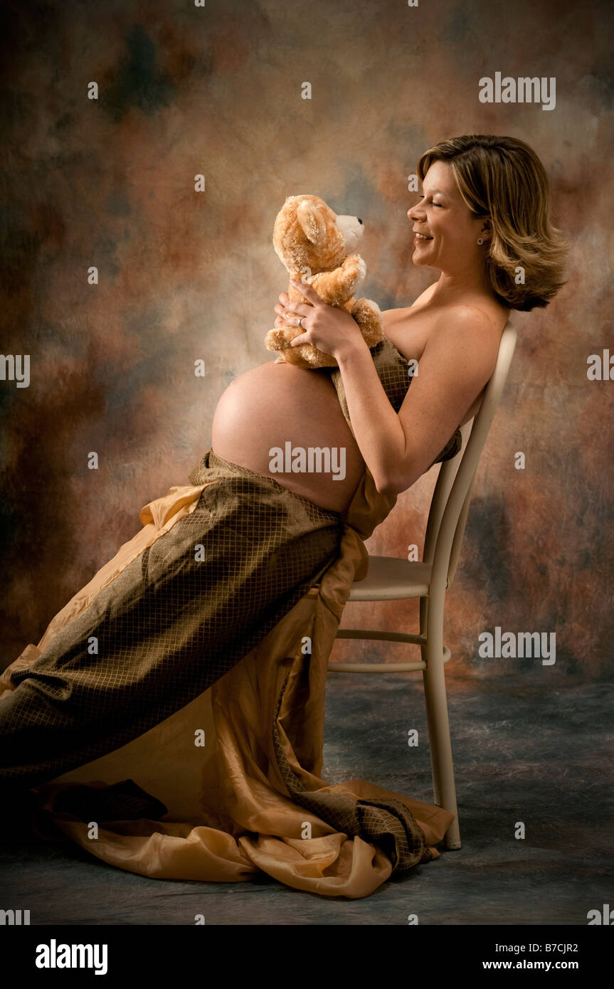 pregnant erotic -porn Stock Photo - pregnant woman with child's toy sitting in chair