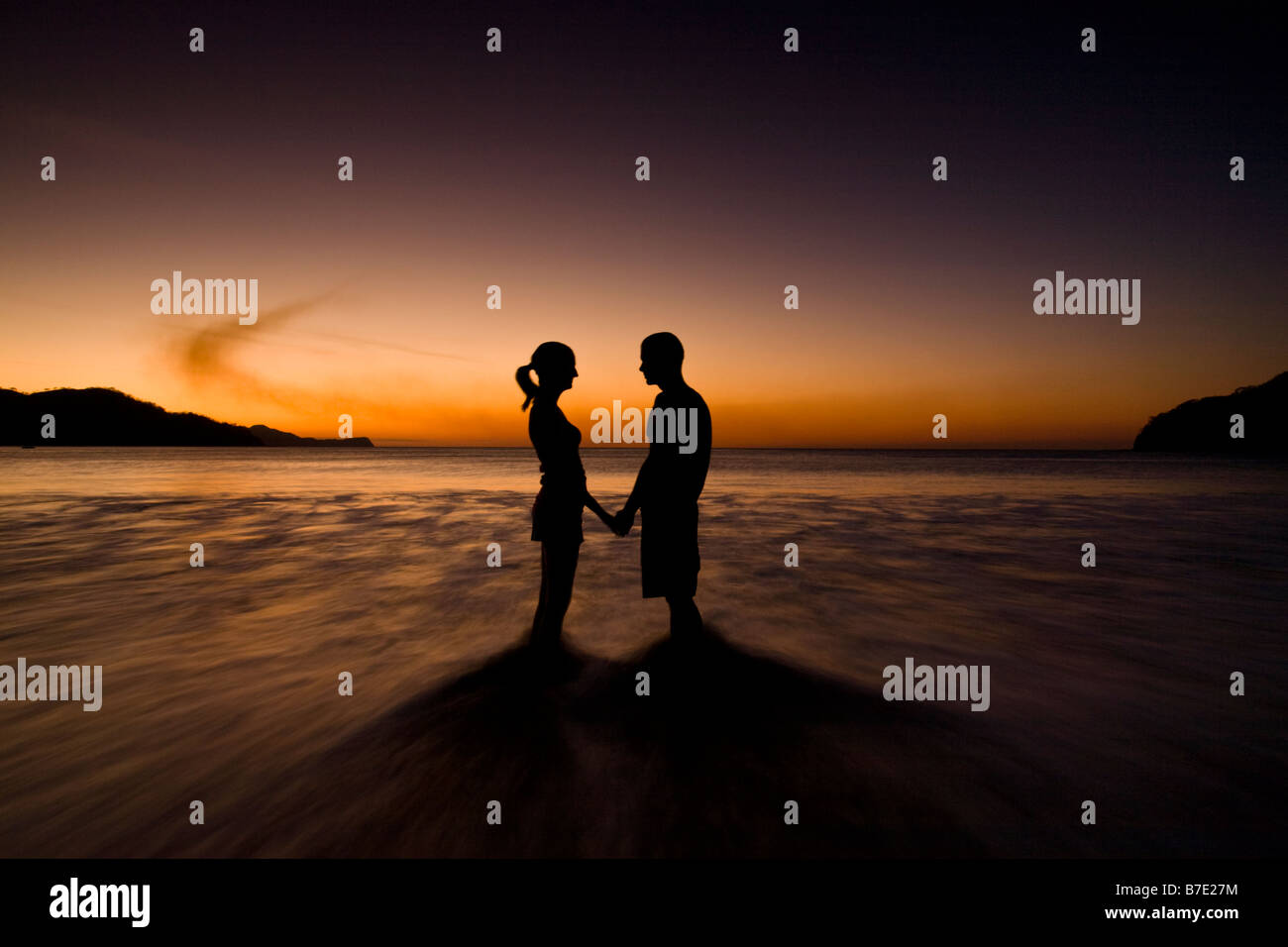 Silhouette of young couple holding hands on the beach and facing ... for Couple Holding Hands Silhouette Sunset  61obs