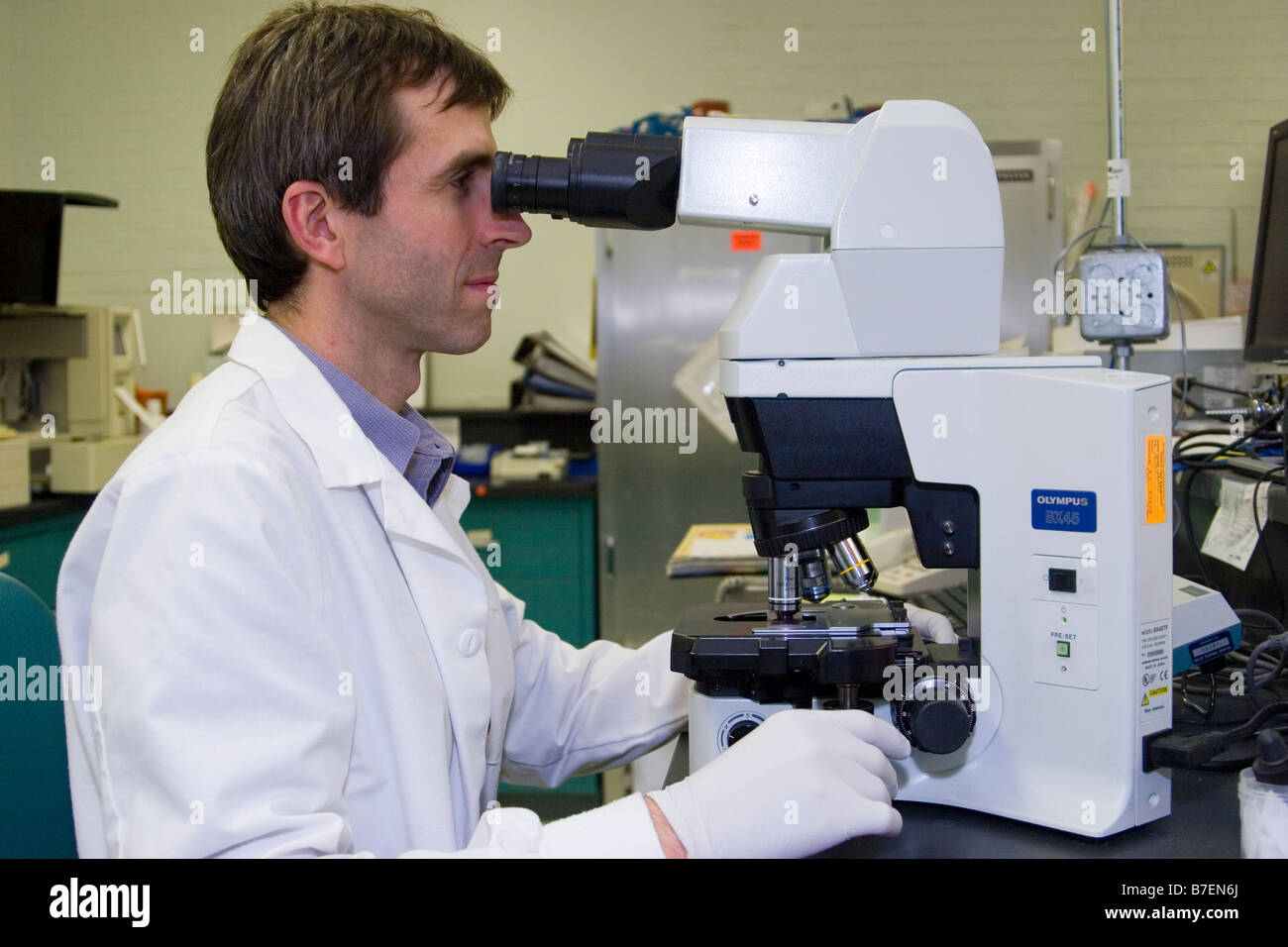 Laboratory technician looks through a microscope searching – Photo Lab Technician