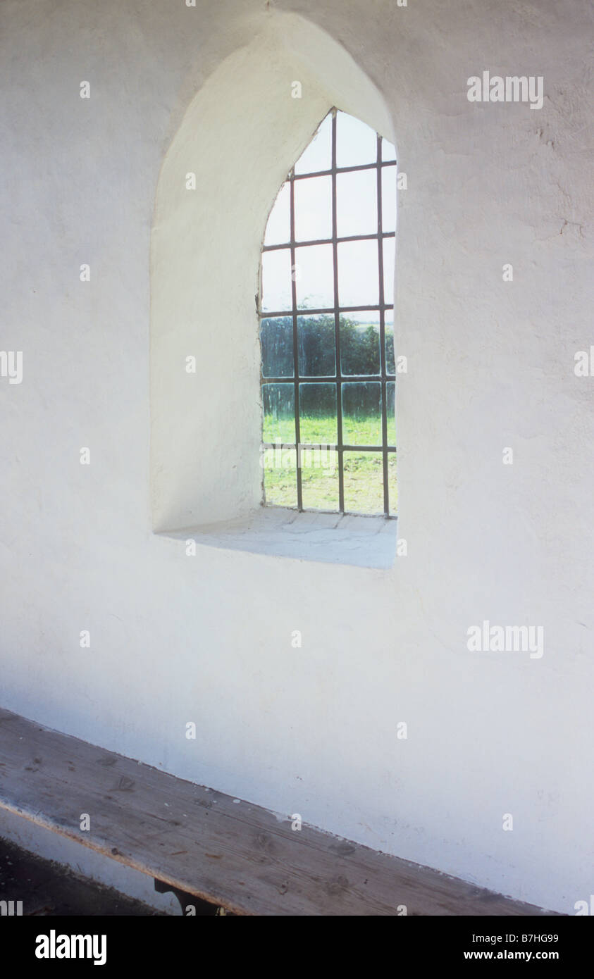 Interior view of small room or lobby or porch or hall with plain walls square leaded arched window and simple wooden bench