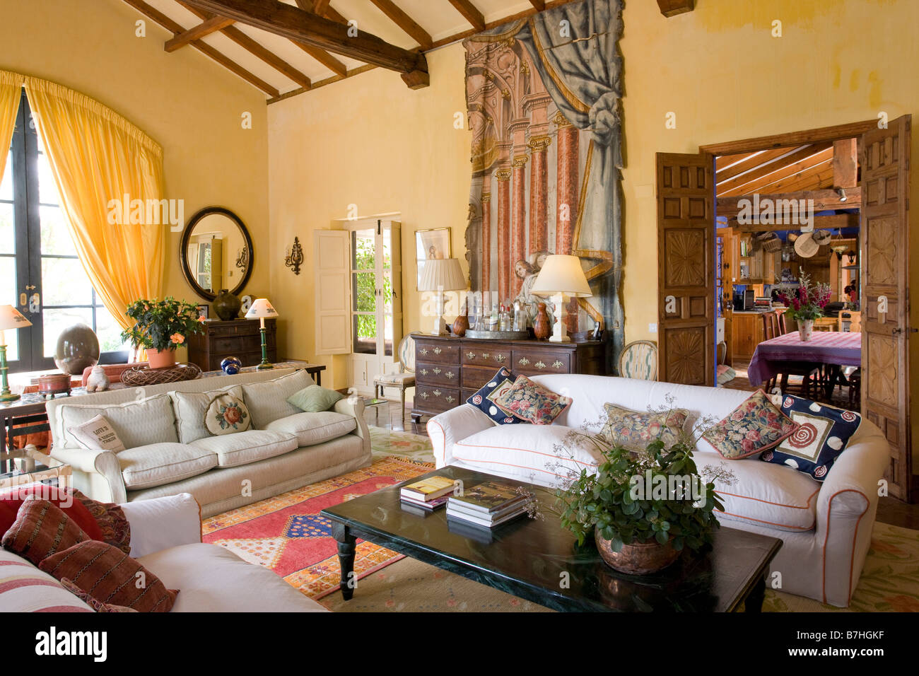 Spanish Living Room Design. Large white sofas in yellow Spanish living room with trompe l oeil curtain  and pillar painted on wall beside doorway to kitchen