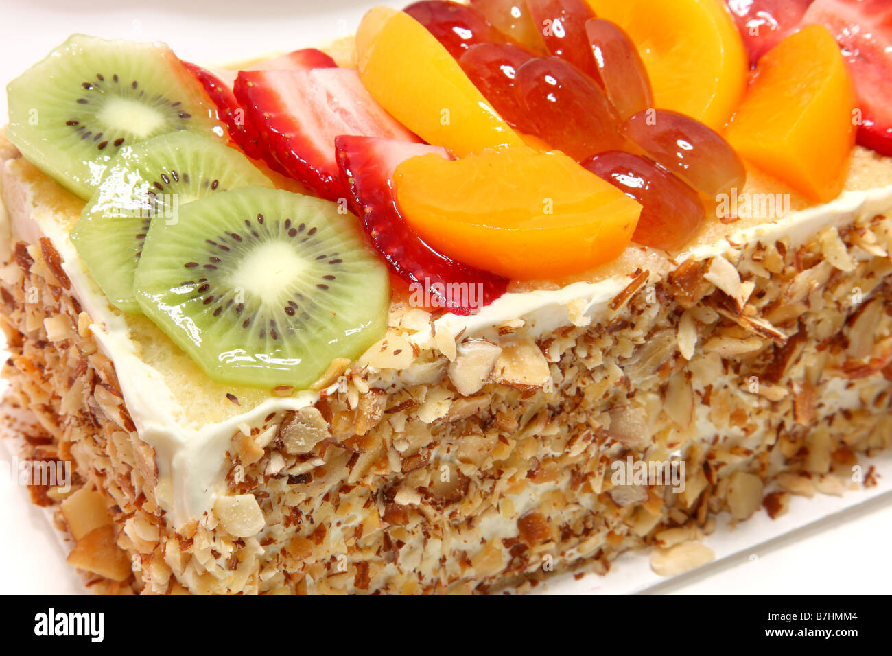 Yellow cake with fruit glaze and fresh strawberry kiwi grape and