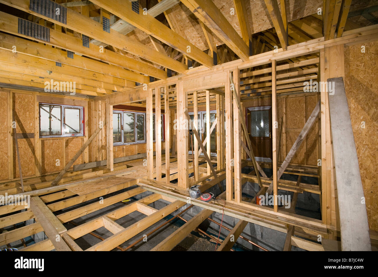 Interior of a timber framed house under construction in for Timber frame house construction