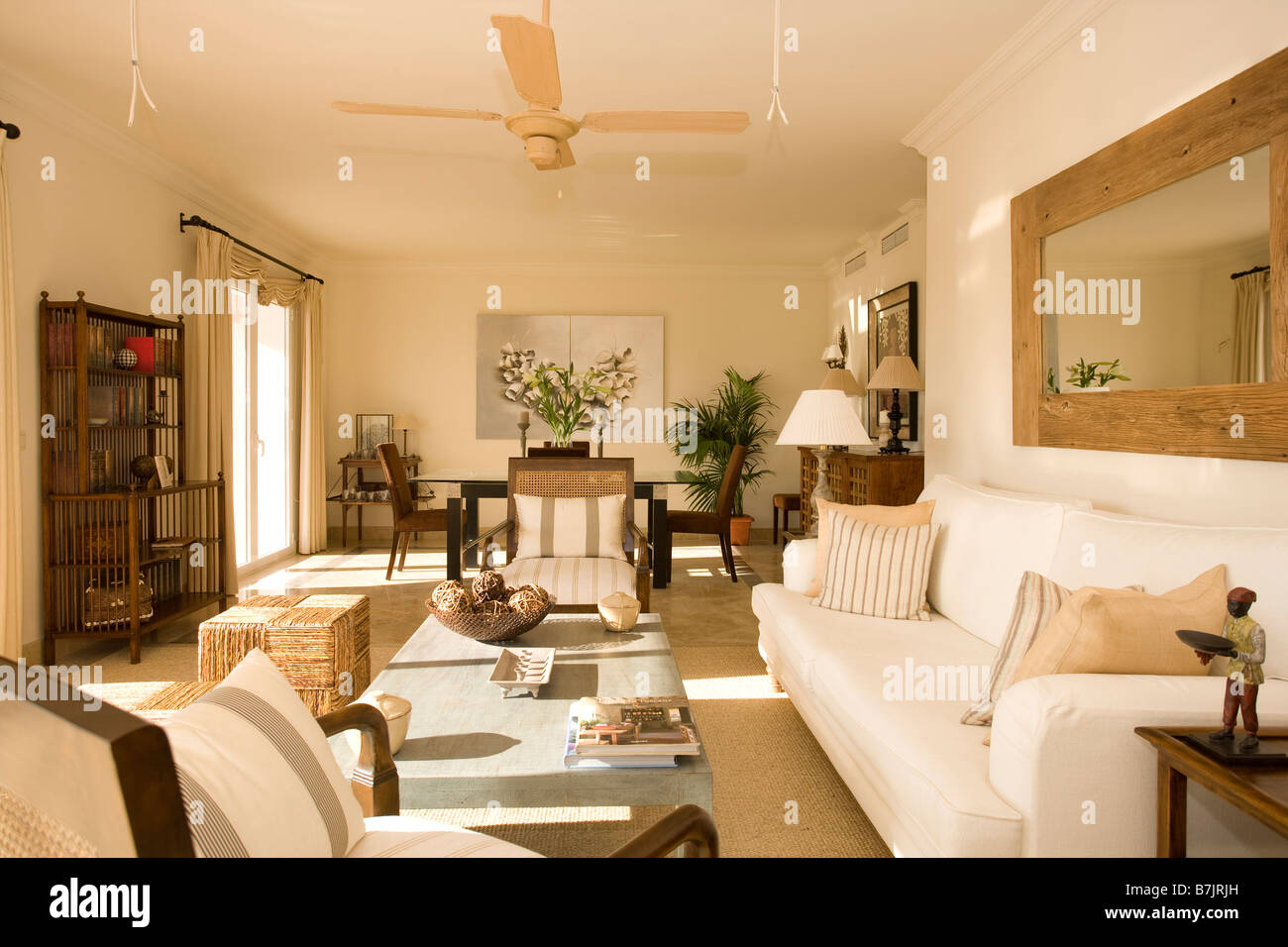 Large Wooden Mirror Above Cream Sofa In Modern Openplan Living And Dining Room With Ceiling Fan