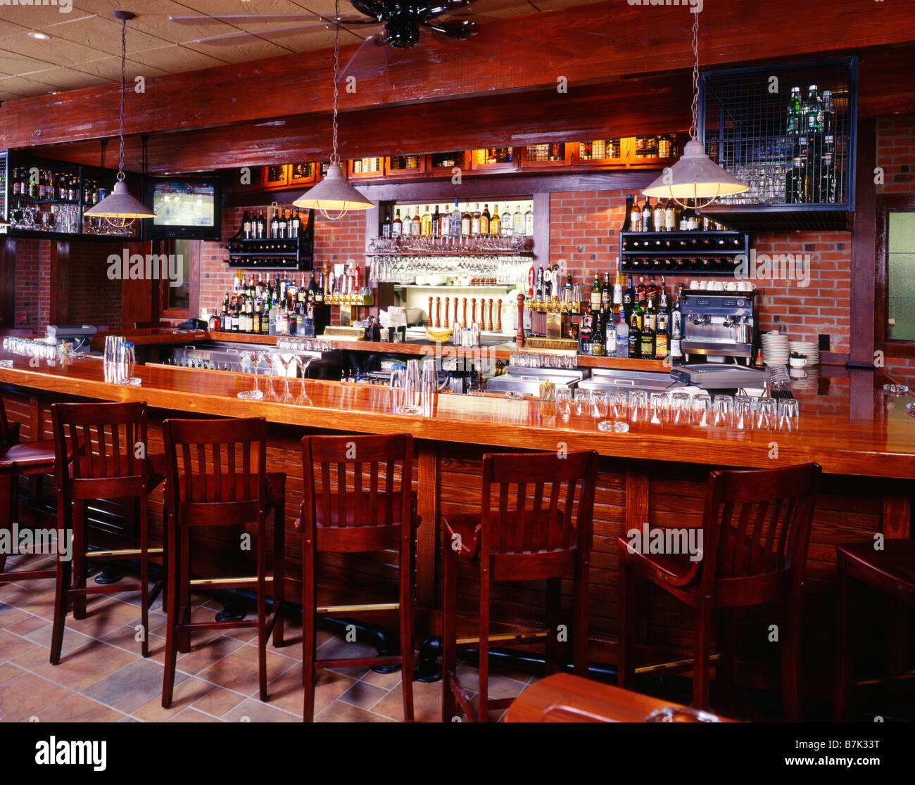 wood and brick bar interior with liquor bottles glasses and stock