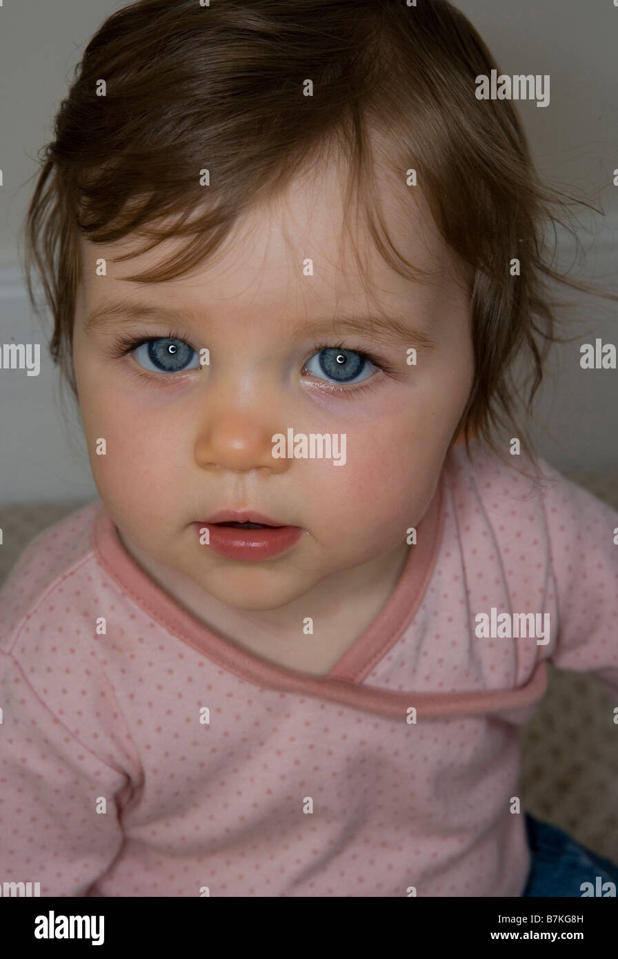 a baby girl with bright blue eyes stock photo royalty