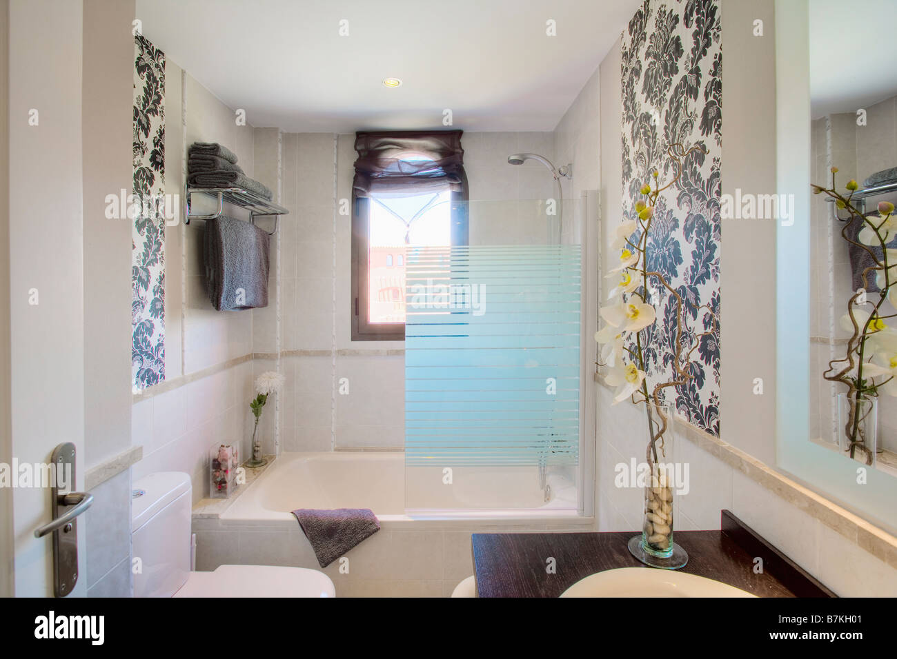 small modern bathroom with opaque glass shower screen on bath and small modern bathroom with opaque glass shower screen on bath and large leaf print wallpaper on two walls