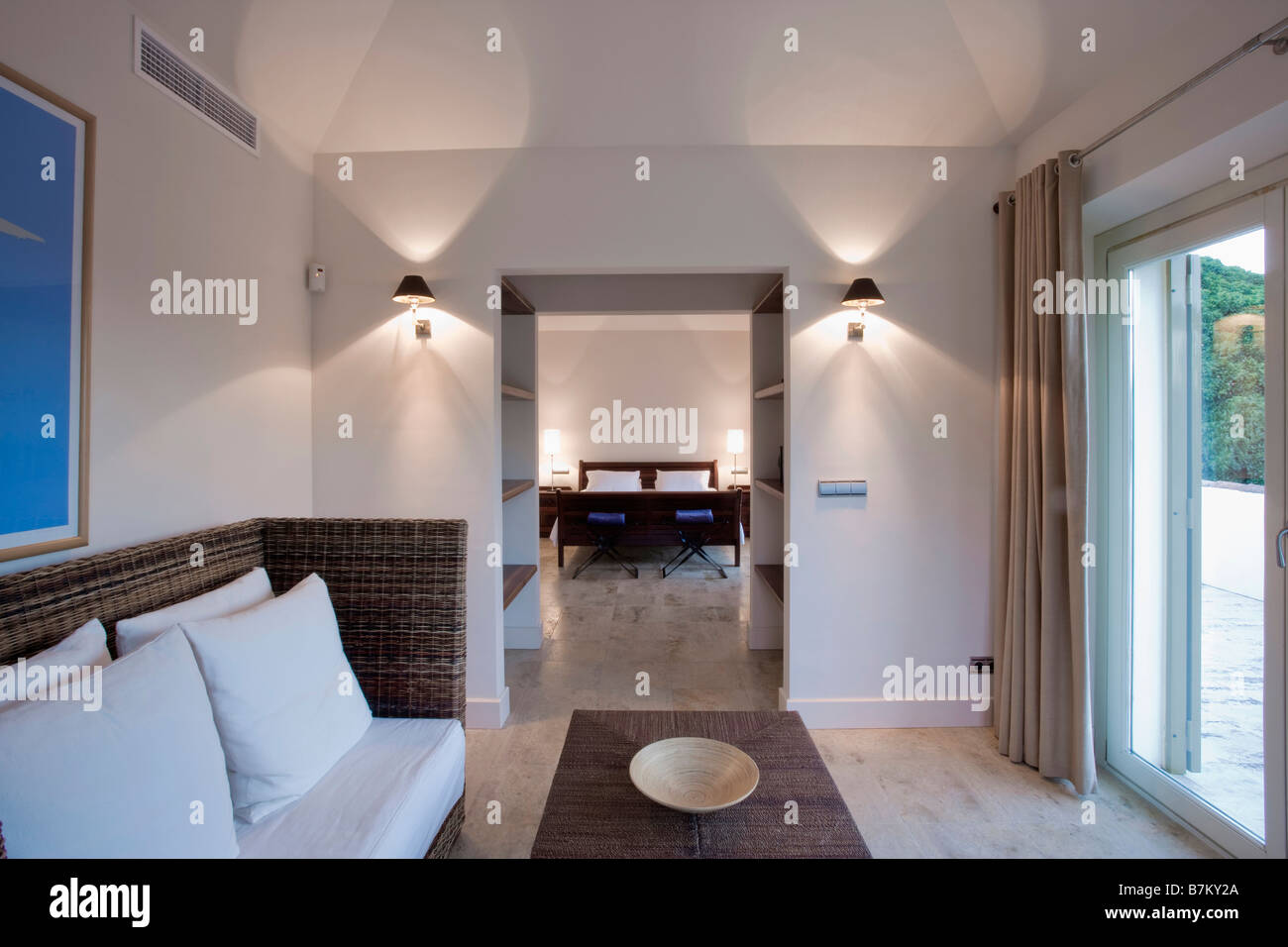 Lighted Wall Lights On Either Side Of Doorway Living Room In Modern Spanish Hotel Suite