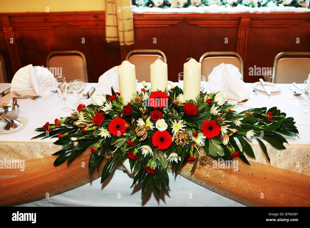 Floral Top Table Flower Display Centre Piece At A UK Wedding Reception With Festive Winter Xmas Colours Flowers