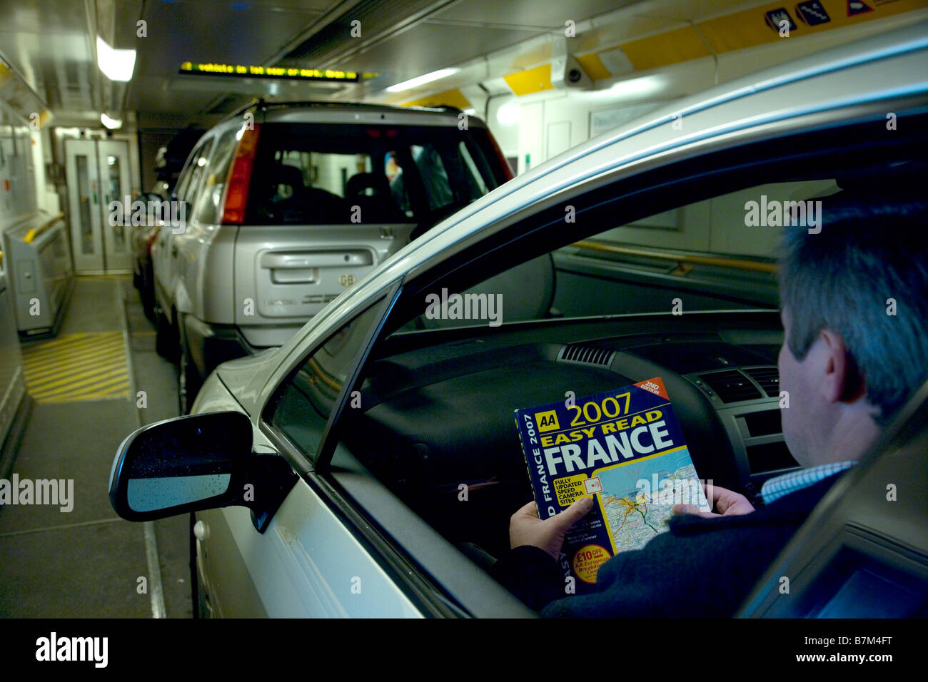 Cars inside channel tunnel train with man looking at