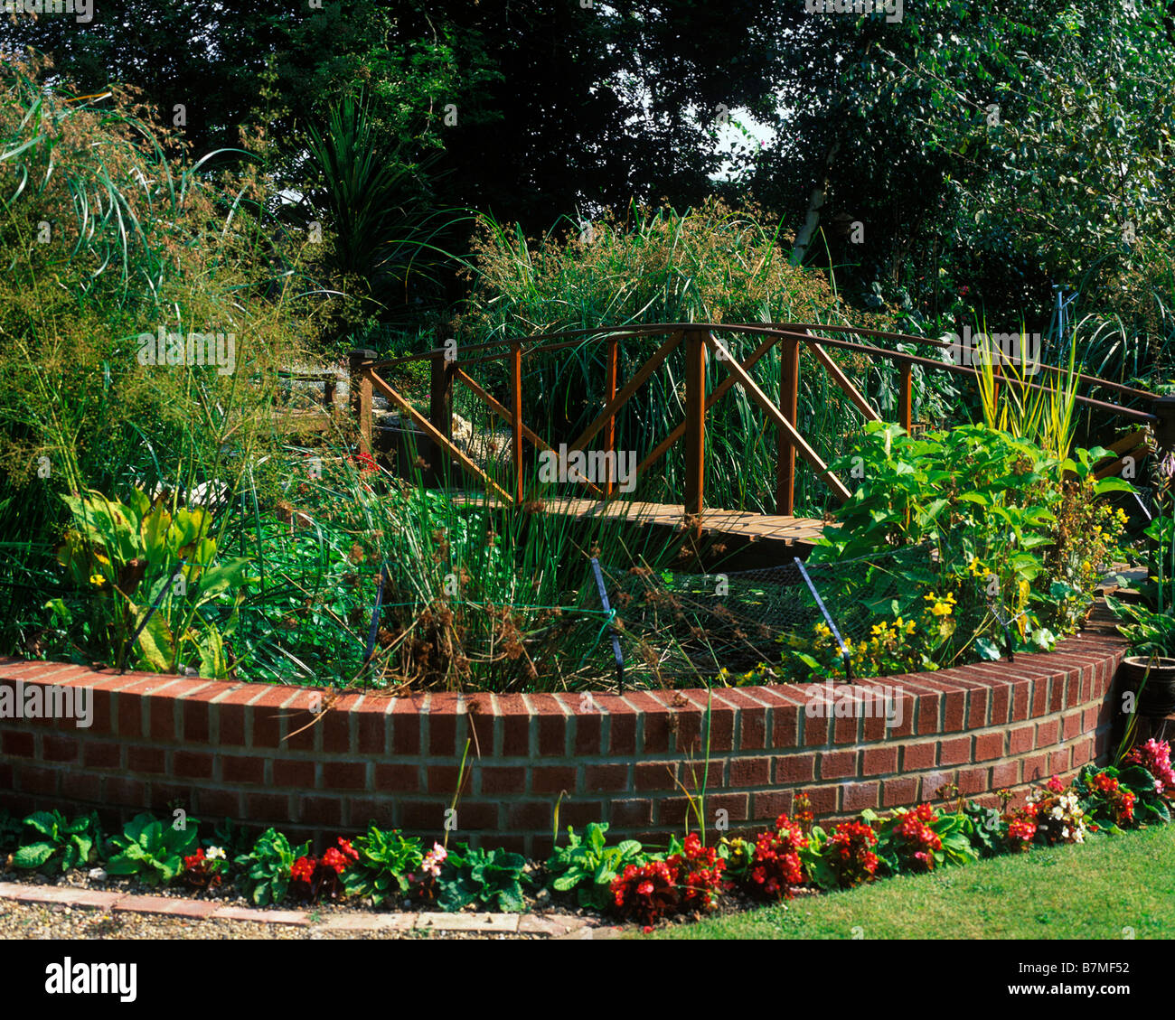 RAISED GARDEN POND WITH BRICK SURROUND AND BRIDGE Stock Photo