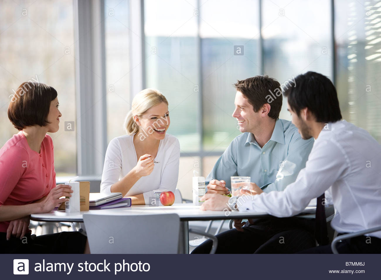 office canteen. four office colleagues eating lunch in an canteen or cafe