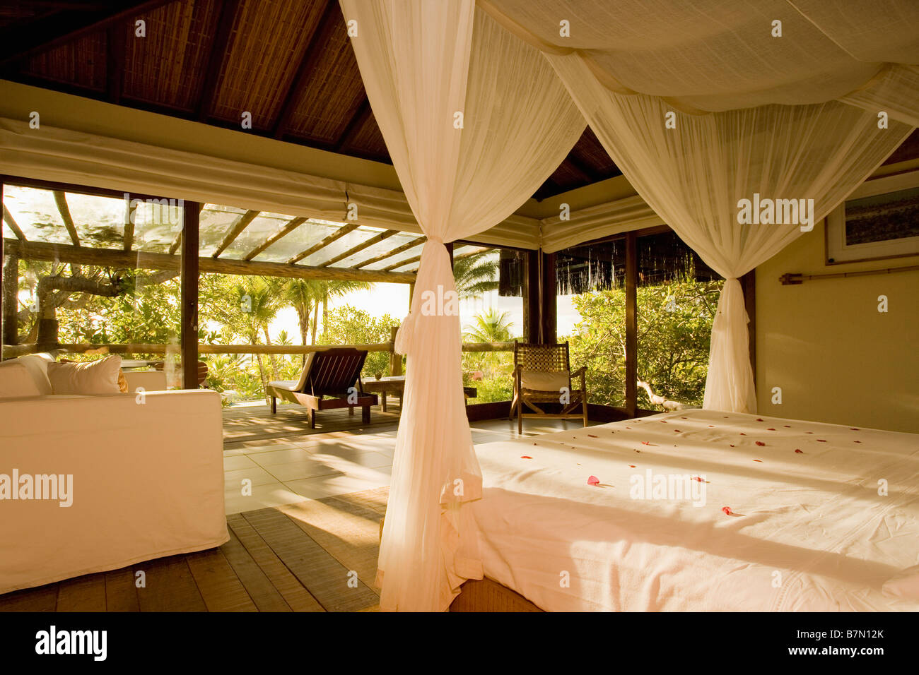 Bedroom ceiling drapes - Stock Photo White Voile Drapes And Bedlinen In Modern Openplan Bedroom With Veranda In Beach House In Brazil