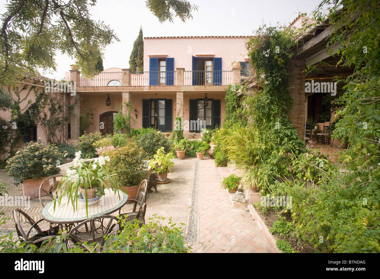 Stock Photo   Table And Chairs On Patio In Spanish Courtyard Garden With  Herringbone Brick Path To Villa With Blue Shutters And Balcony