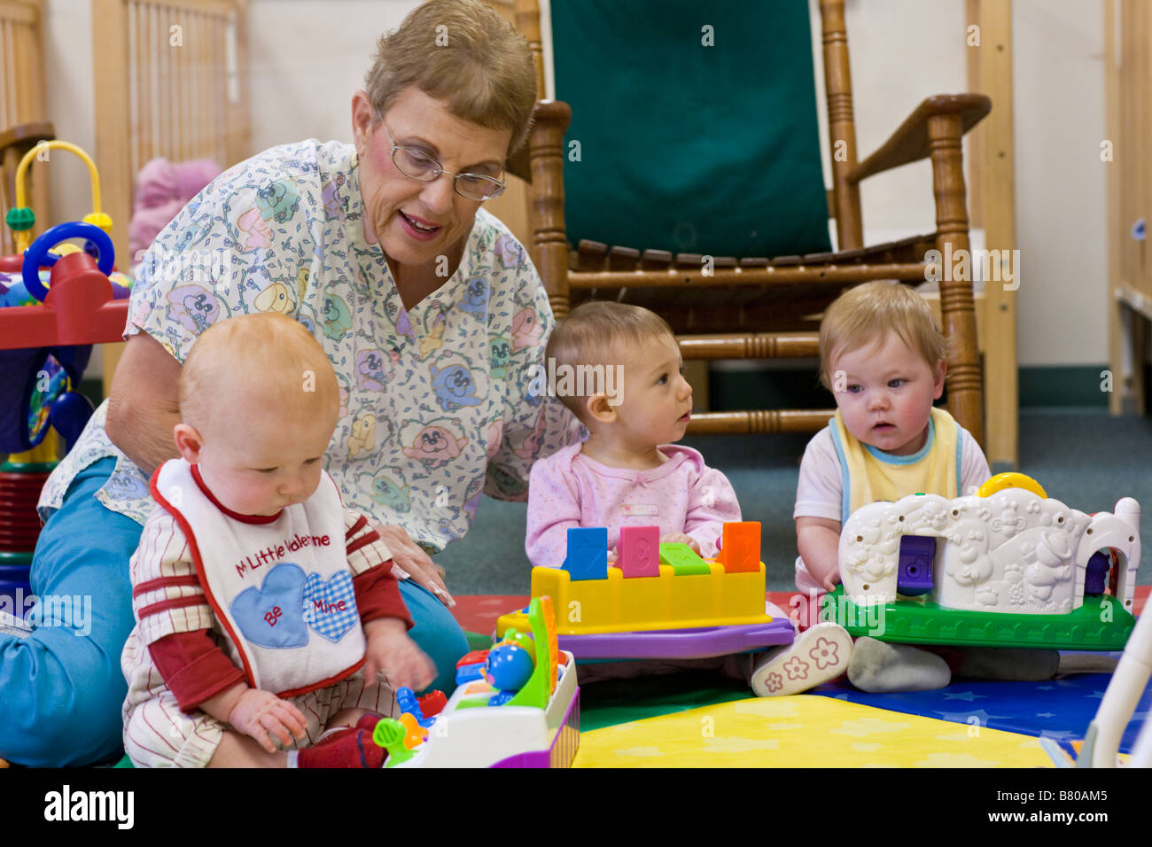 Day Care Toys : Senior preschool daycare worker using bright colored toys