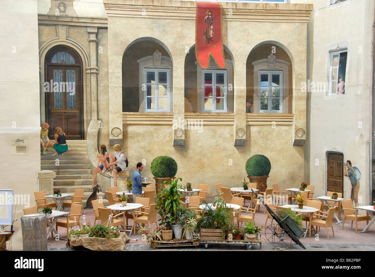 waiter in a restaurant terrace photorealistic painting on the stock photo waiter in a restaurant terrace photorealistic painting on the house wall montpellier france europe