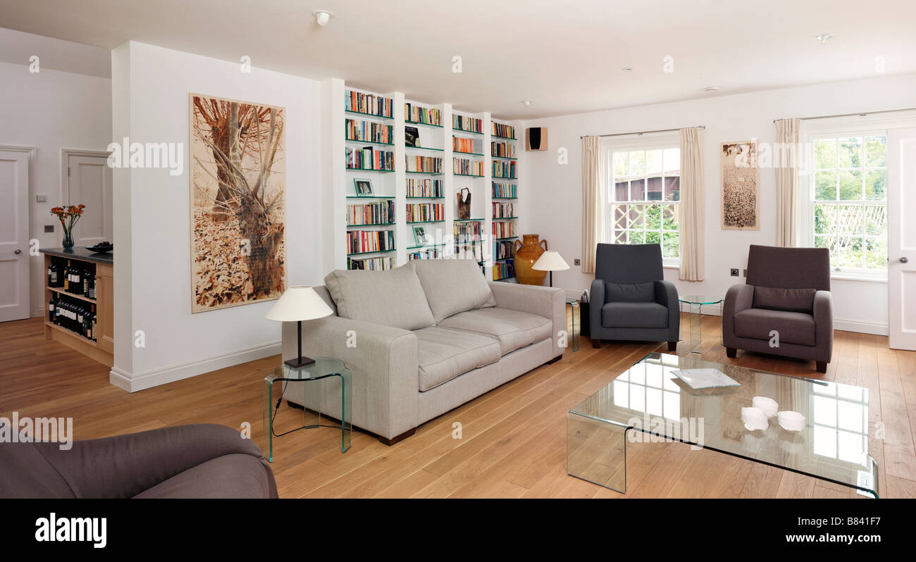 Stock photo modern living room with neutral sofas and large wall book case and glass coffee table