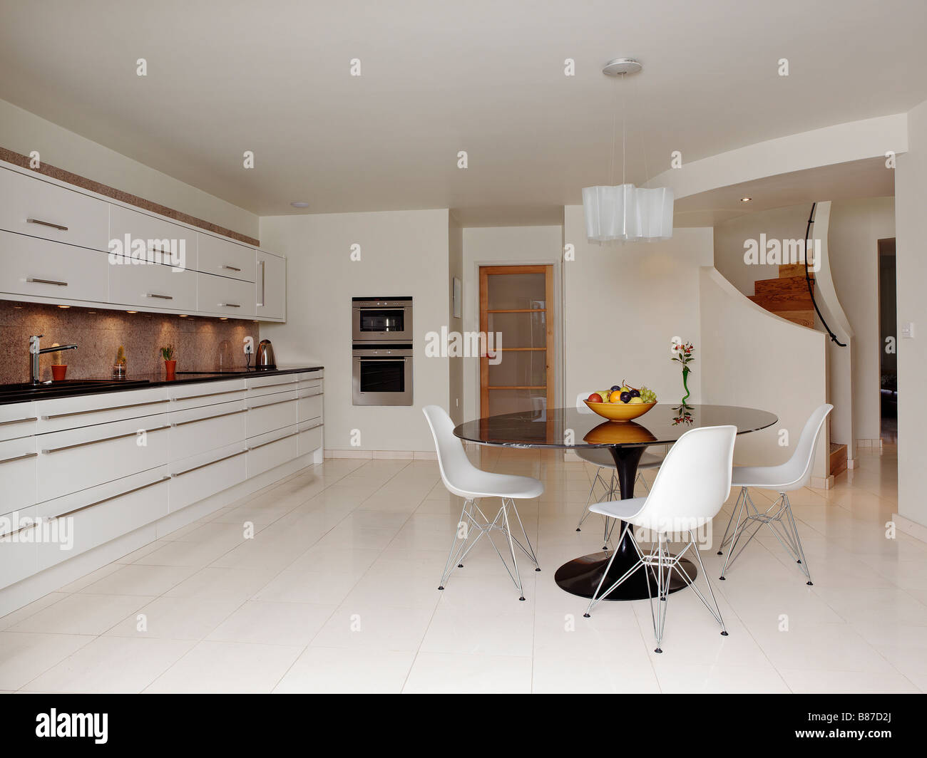 Stock Photo   Contemporary White Kitchen With Round Table And Fruit Bowl  And Spiral Staircase