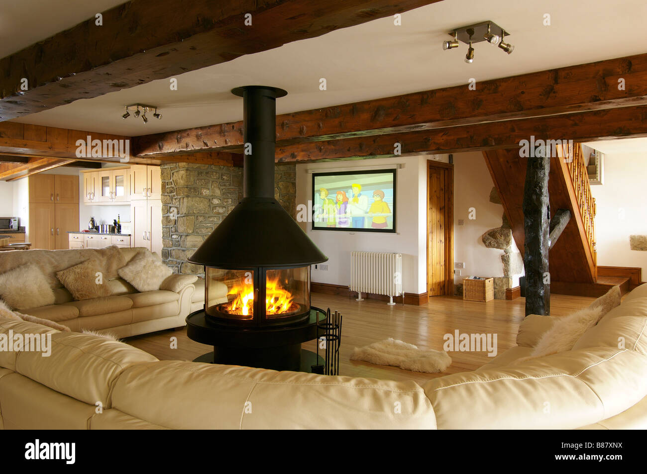 Stock Photo   Living Room With Large Cream Sofa And Central Circular Lit  Fire With Wooden Beams And Large Television Part 79