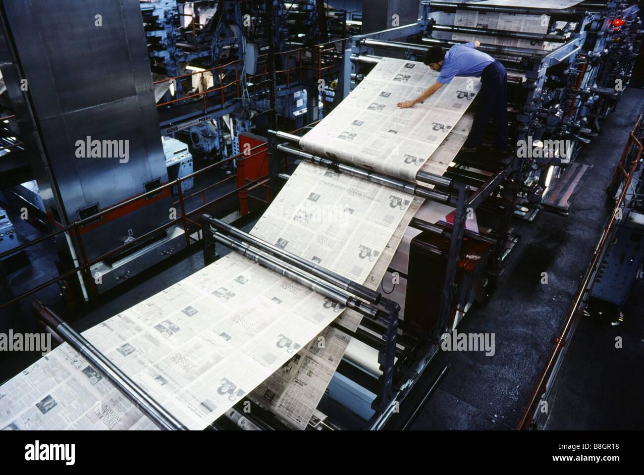 Color press printing - People Working Newspaper Printing On 4 Color Press Pressman Inspects Printed Paper