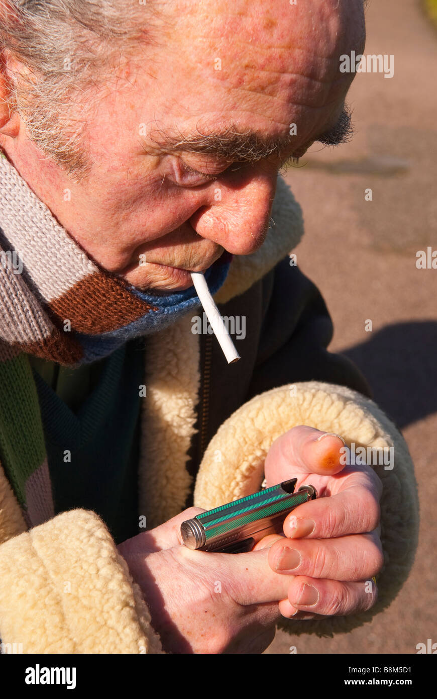 Elderly man lighting his roll up cigarette outdoors ready for smoking & Elderly man lighting his roll up cigarette outdoors ready for ... azcodes.com
