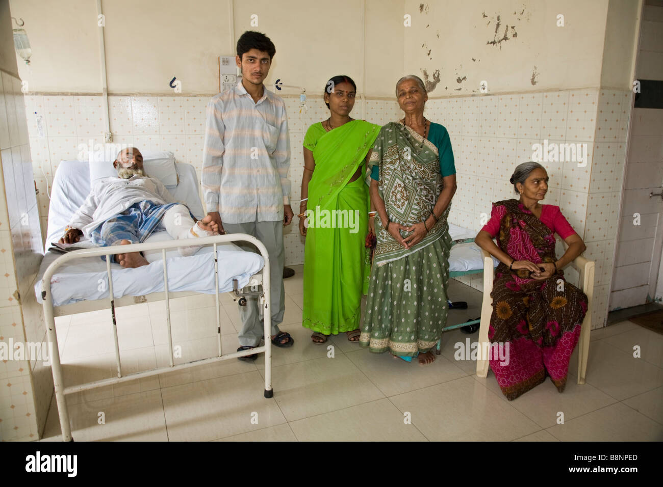 Hospital room with patient and family - Family Members With A Bed Ridden Patient In A General Ward Of The New Civil Hospital