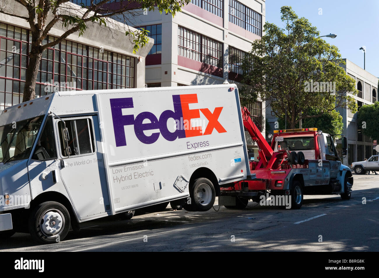 A fedex express hybrid electric delivery van being towed by a tow truck downtown san