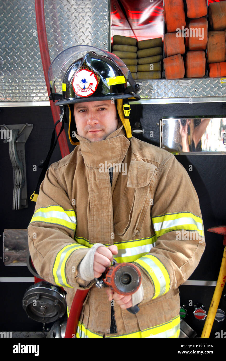 Male Firefighter holding fire hose in front of fire truck ...