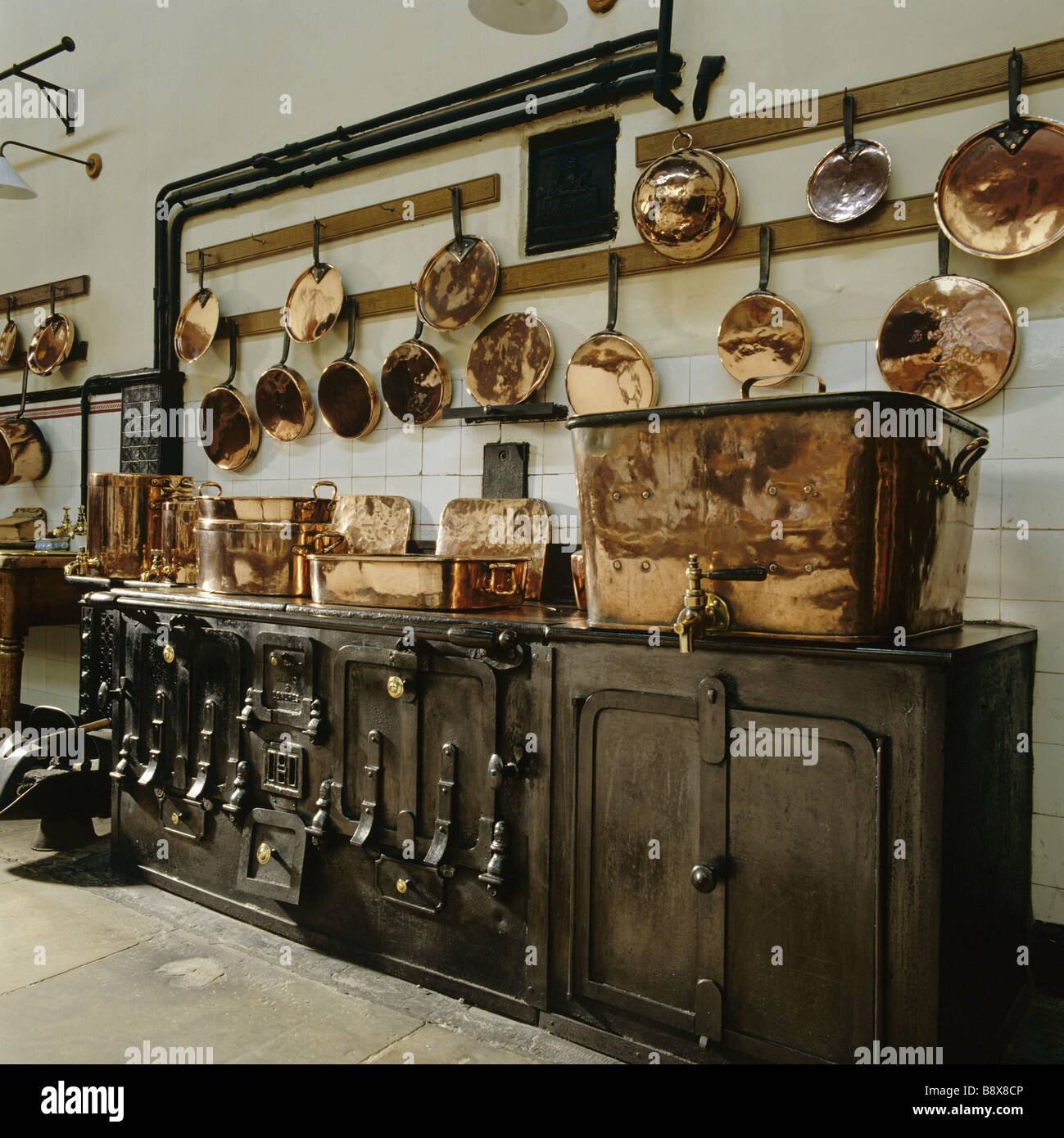 the kitchen at lanhydrock copper pots and pans hang from the wall