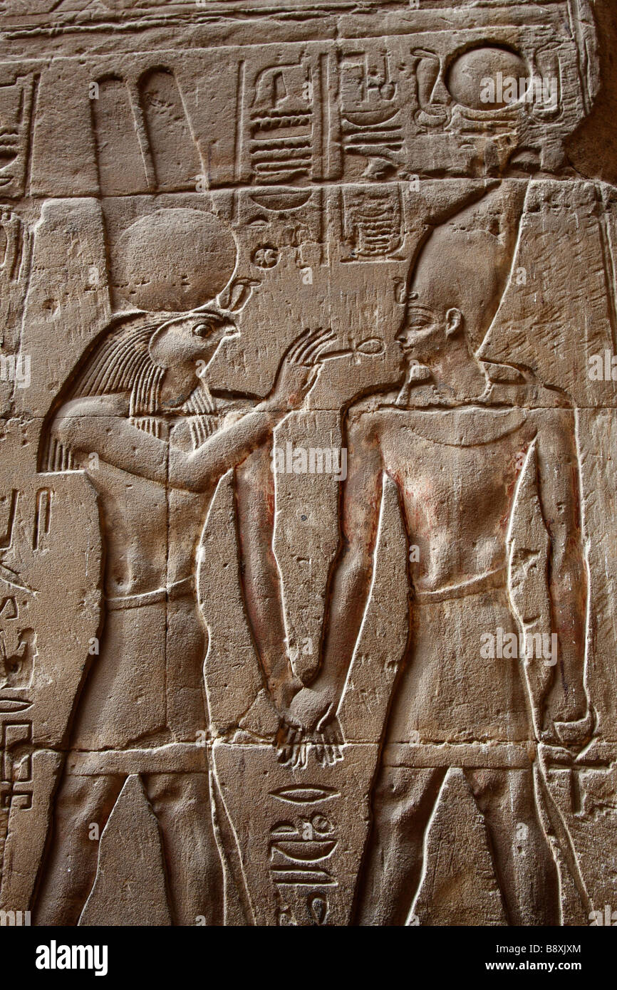 Ancient egyptian hieroglyphics and wall relief showing god