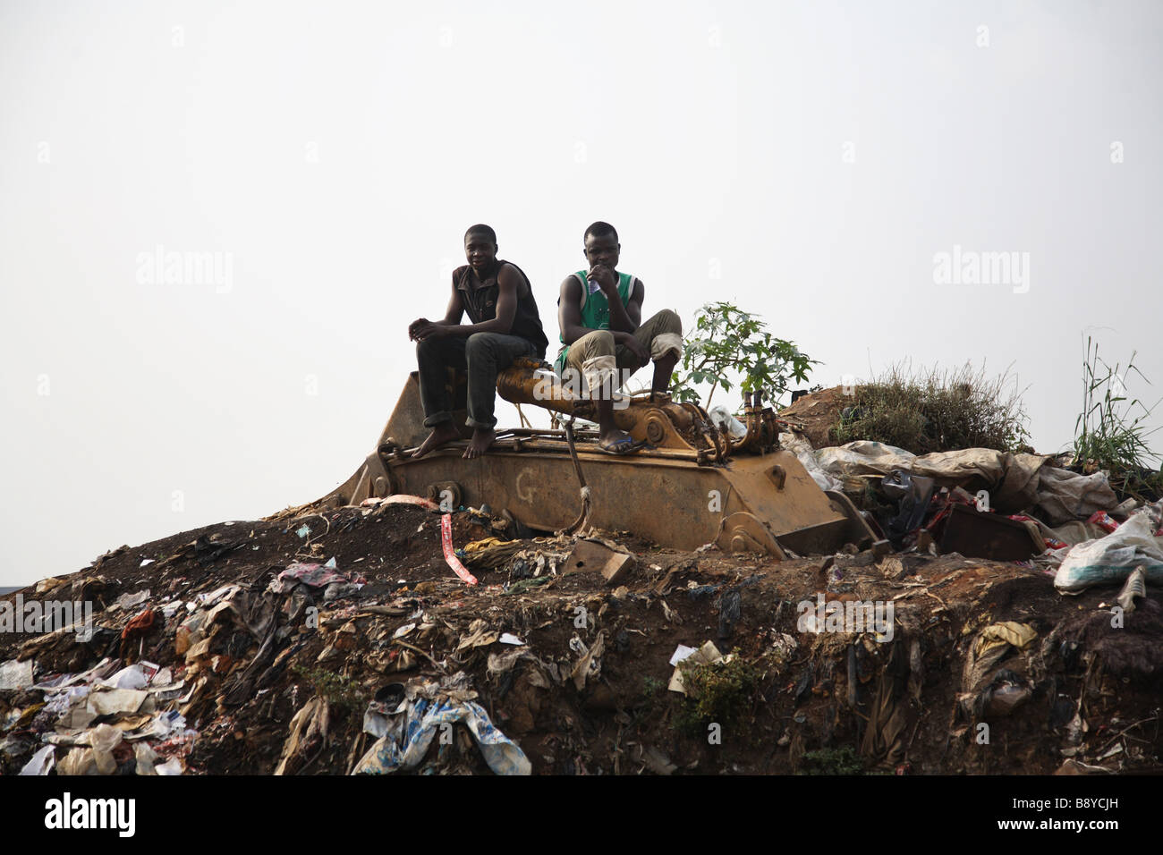 Two men are sitting on top of a mountain of rubbish in Olusosum ...