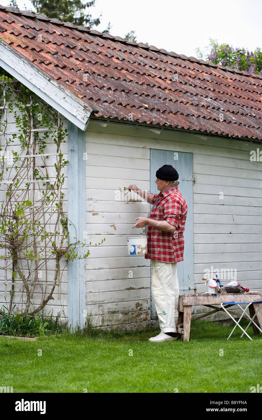Elderly Man Painting His Summer Cottage Sweden