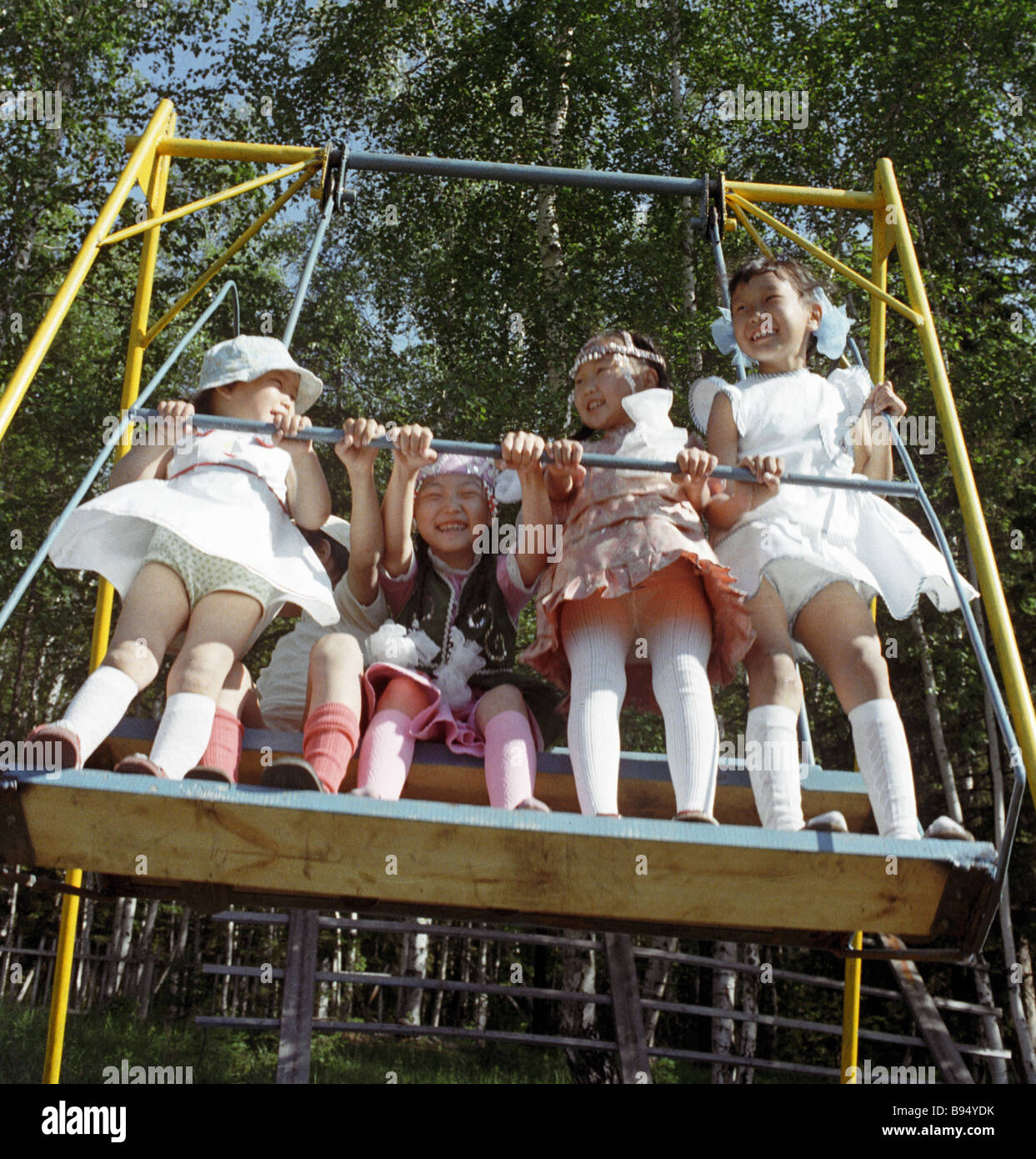 Little girls rocking on a swing Stock Photo, Royalty Free Image ...
