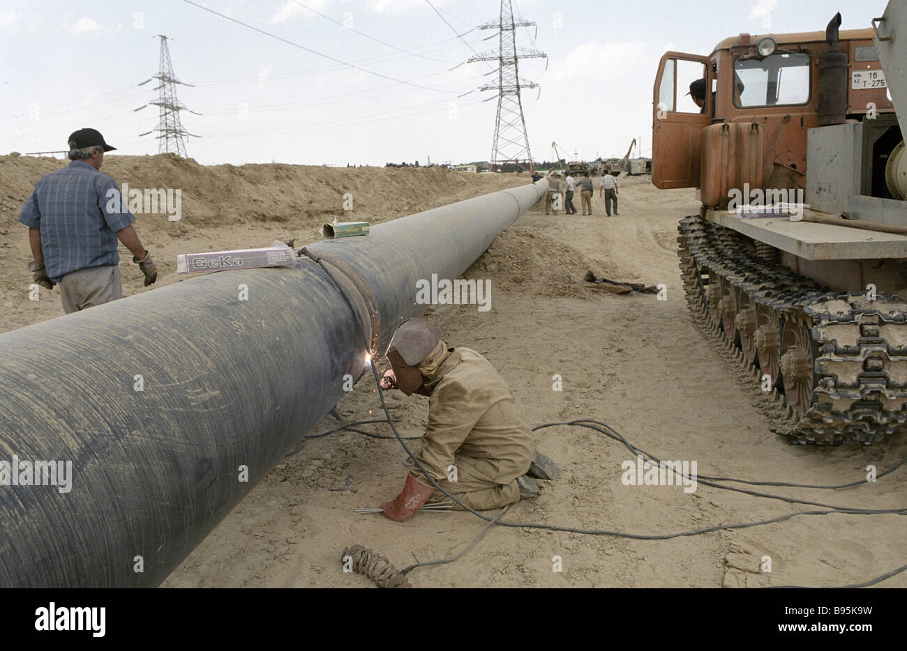 A worker welding pipe seams on the construction site of